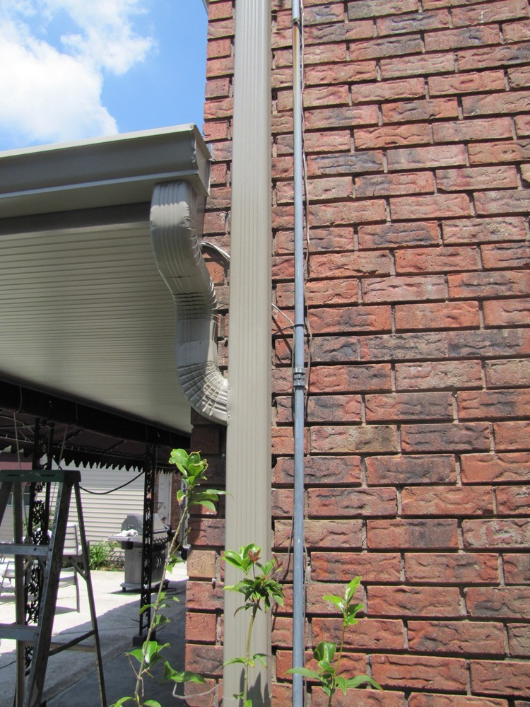 Tan gutters on brick in New Orleans - Strong Shield