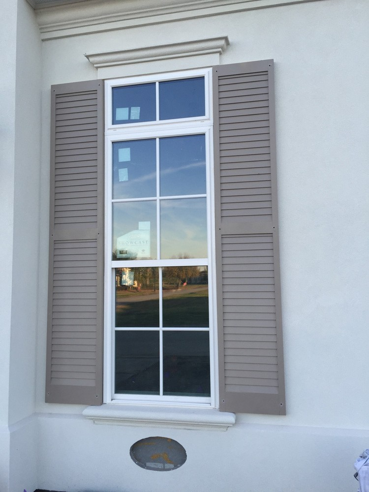 Tan shutters on white home with trimmed windows - Strong Shield