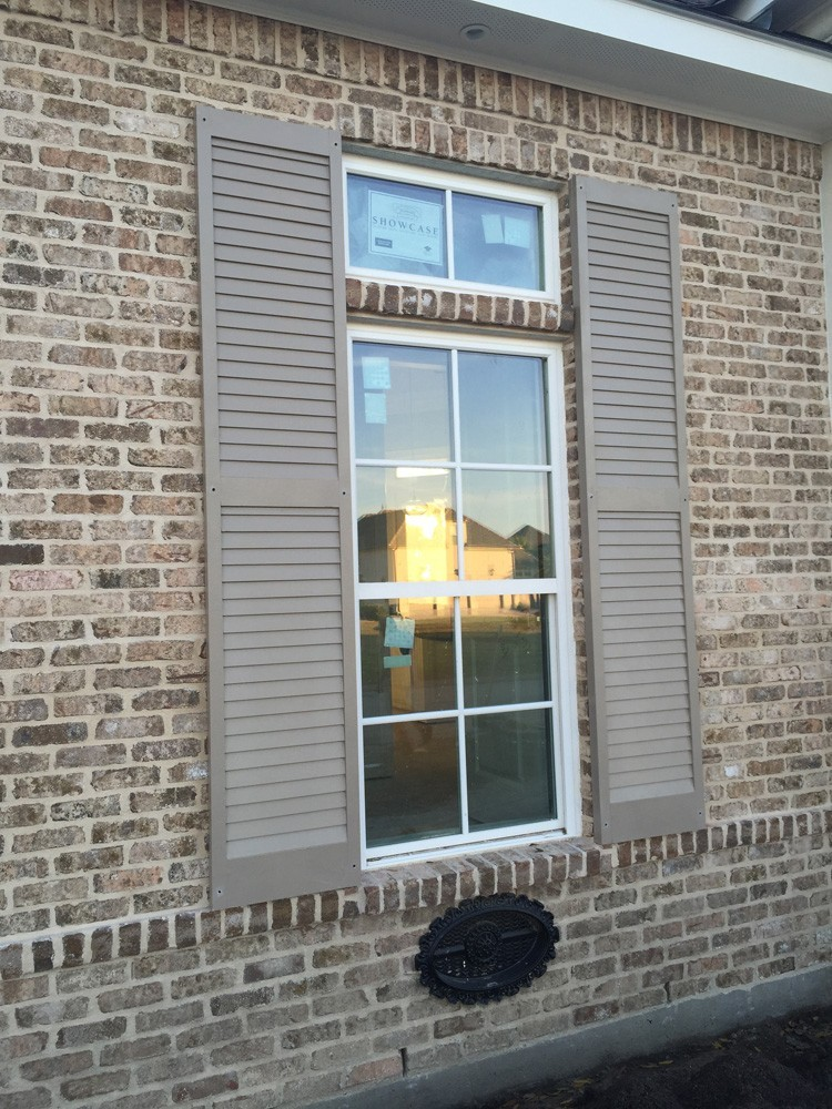 Tan shutters on New Orleans brown brick home - Strong Shield