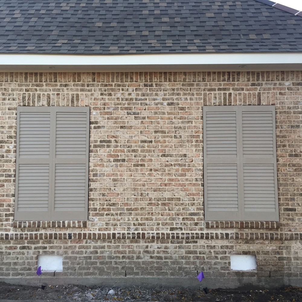 Shutters on brown brick home - Strong Shield