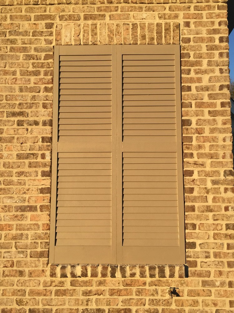 Tan shutters on brown brick in direct sunlight - Strong Shield