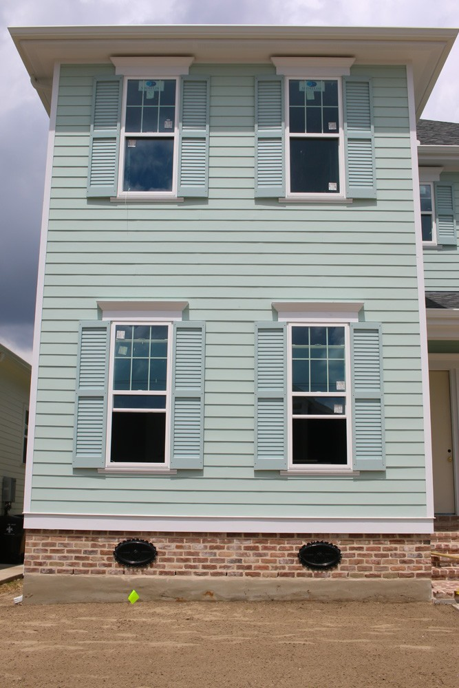 Shutters on green home with red brick in New Orleans - Strong Shield