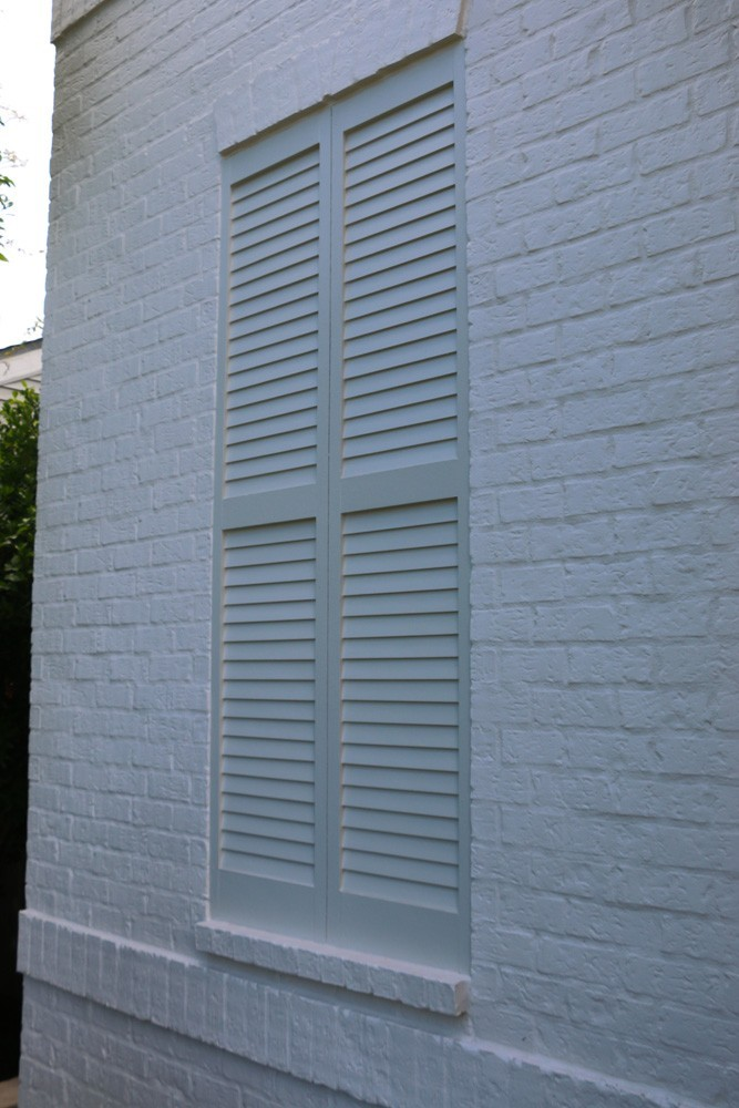 White shutters on white brick home - Strong Shield