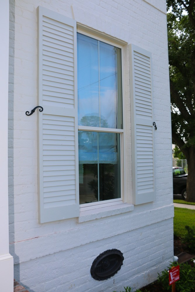 Shutters on white brick home with holdbacks - Strong Shield