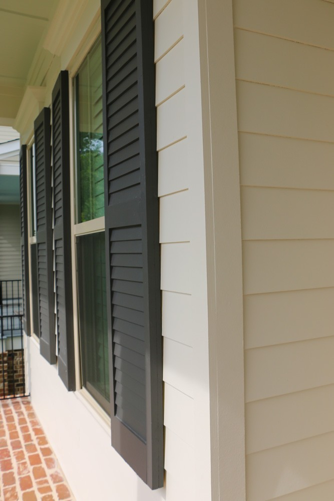 Shutters on white home with brick floor porch - Strong Shield