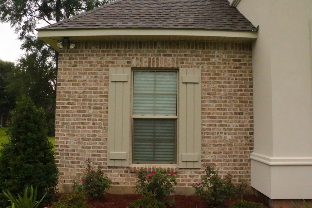 Tan board and batten shutters on Metairie home - Strong Shield