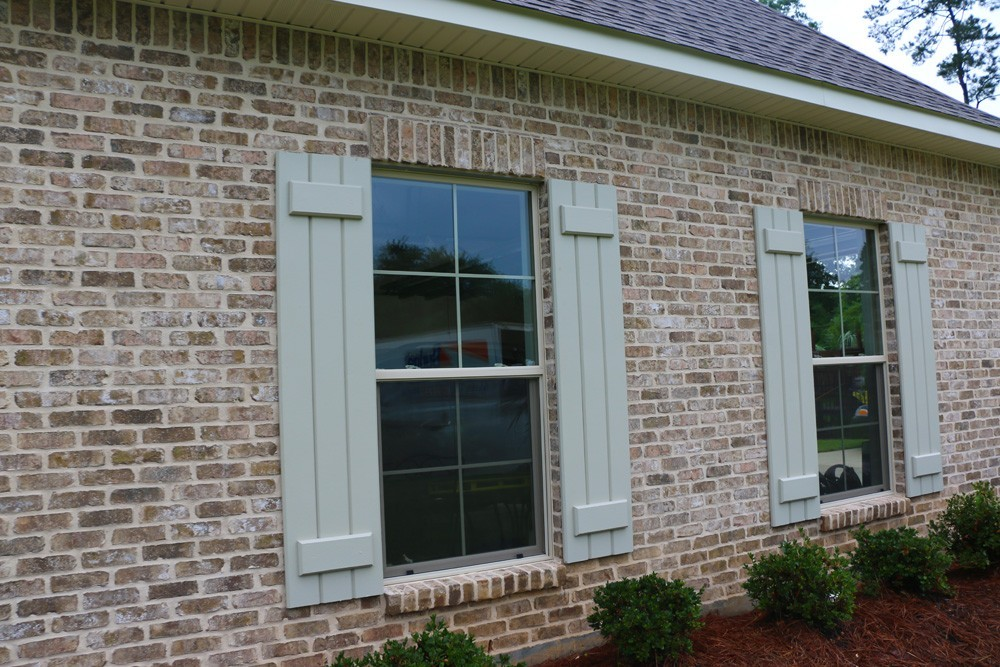Light colored board and batten shutters - Strong Shield