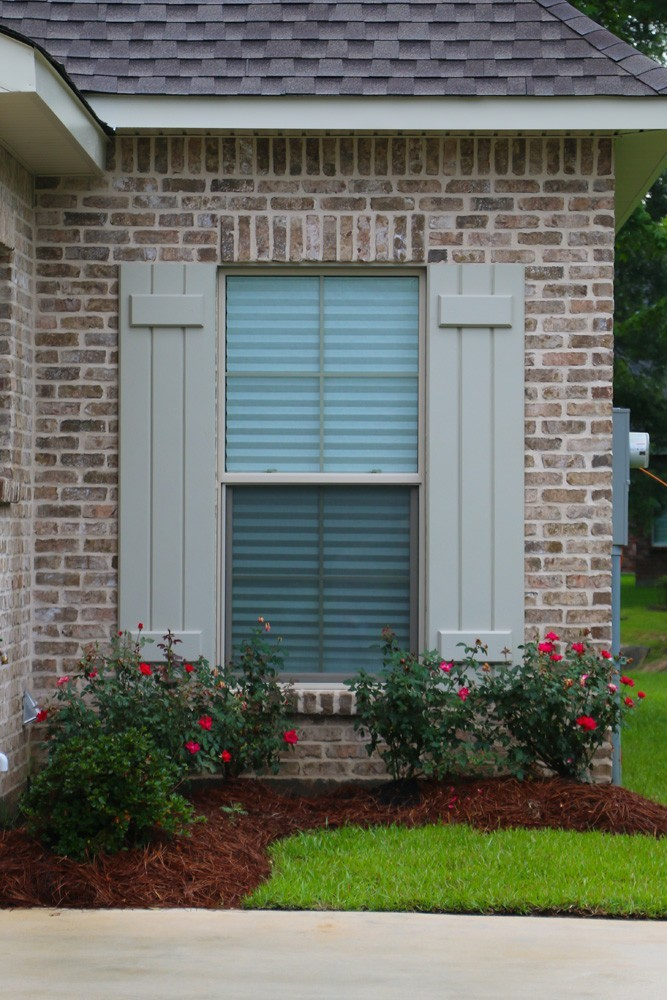 Light sage shutters on brown brick - Strong Shield