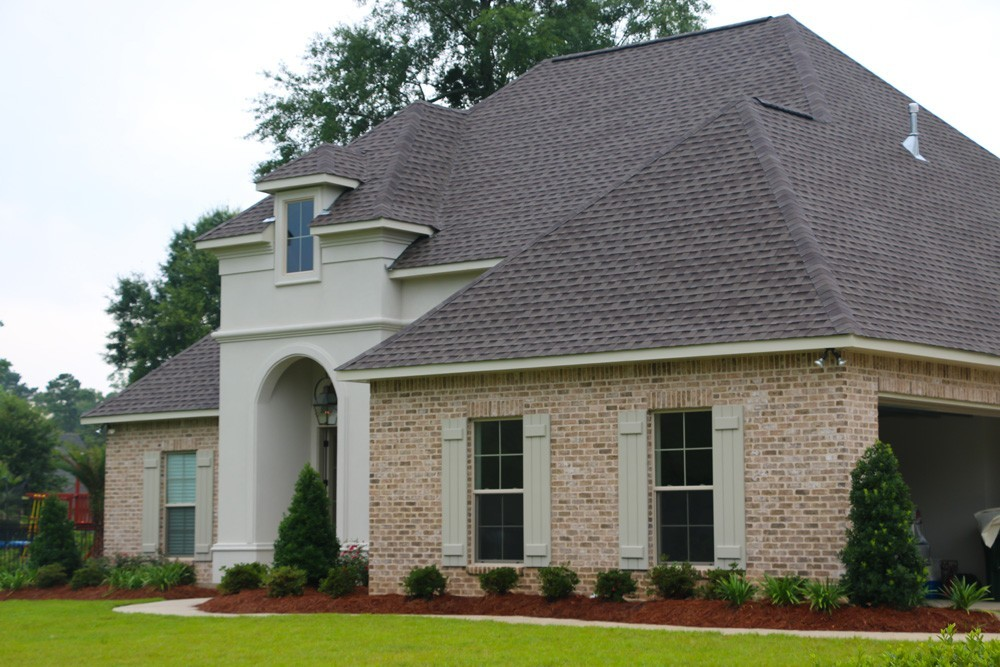 Sage shutters on tan brick and light grey stucco home - Strong Shield