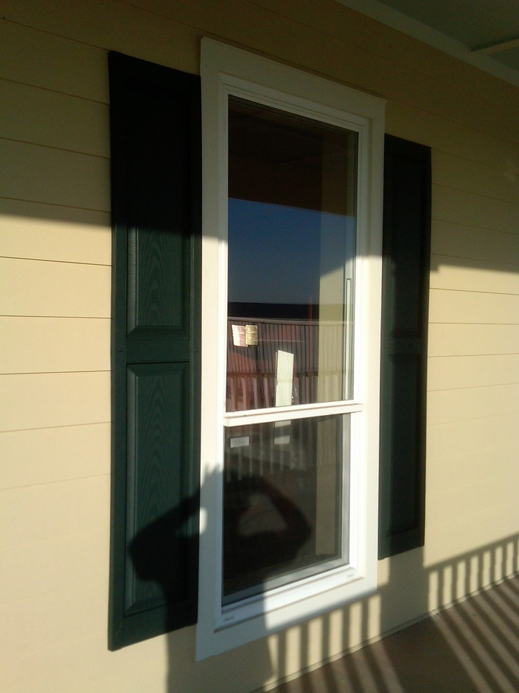 Dark raised panel shutters on hardie siding - Strong Shield