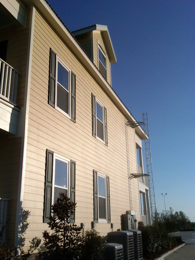 Raised panel shutters on two story hardie home - Strong Shield