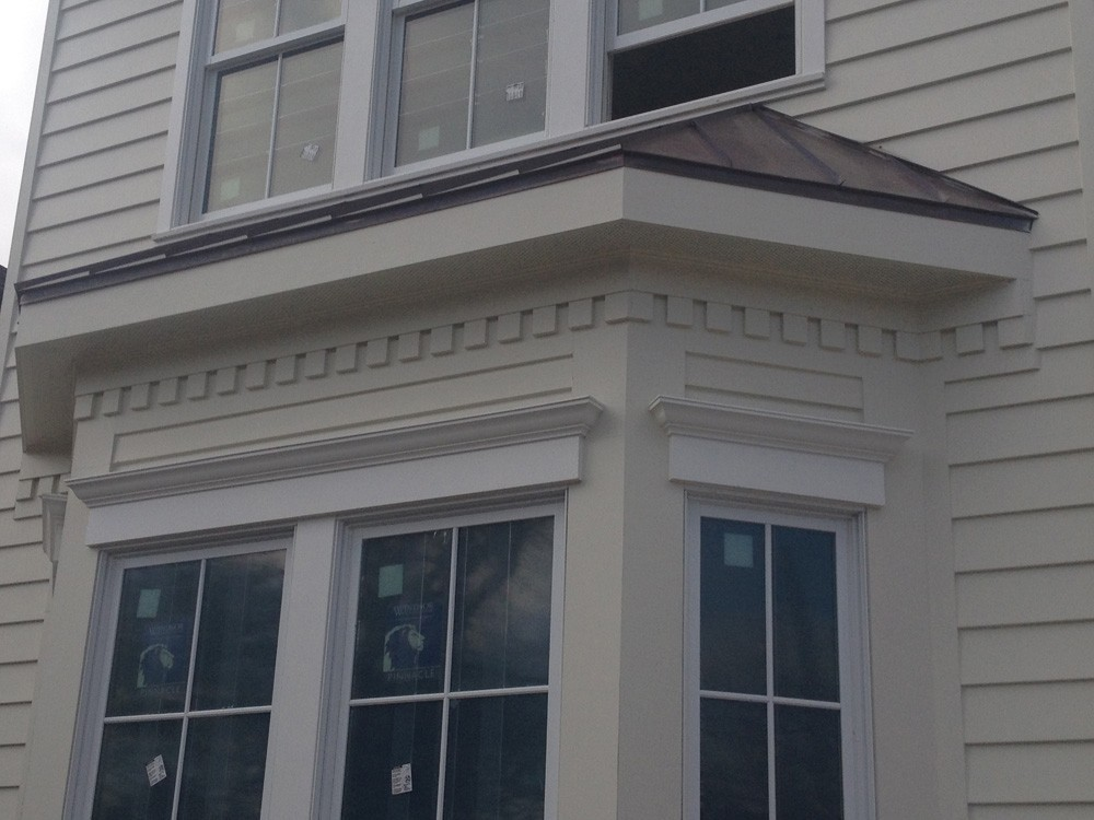 Dentil molding below eaves and molding above windows - Strong Shield