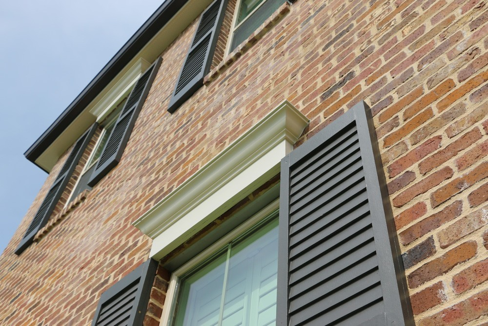 Louvered panel shutters with craftsman window top trim - Strong Shield