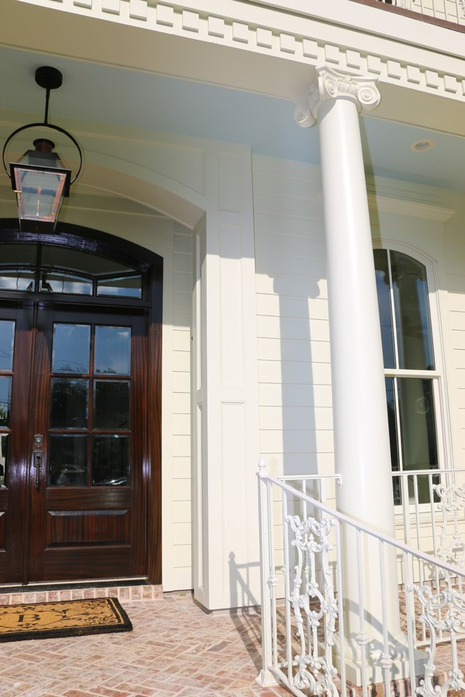 Round columns, dentil molding, and iron railing on New Orleans home - Strong Shield